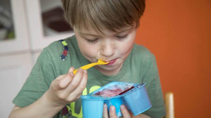 Foto Junge mit süßem Jogurt